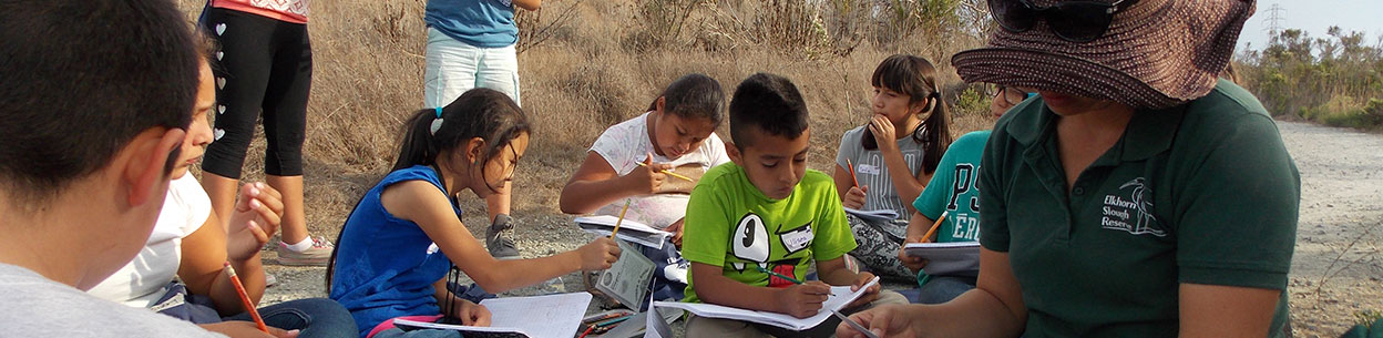 children_sitting_on_beach_writing_on_paper
