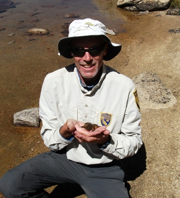 Jim smiling and holding a frog beside a lake