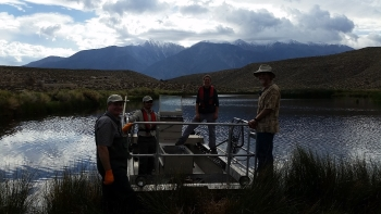Biologists standing on an electroshocking boat on a lake