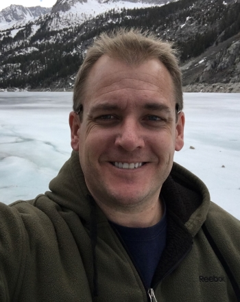 Russell smiling with a frozen alpine lake in the background