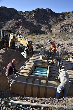 Four men place a 2,300-gallon plastic tank into a rectangular hole in the southern California desert.