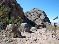 Two fake rocks and a small solar panel on a post, near real rocky terrain in the southern California desert