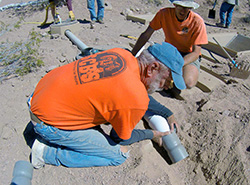 Two men in orange T-shirts place water pipes into a trench in the desert
