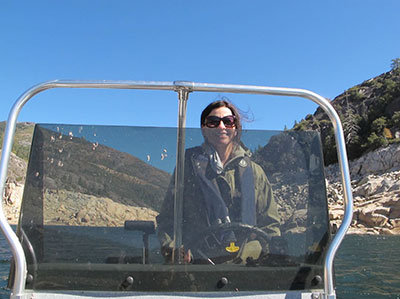 California Department of Fish and Wildlife Scientist Angie Montalvo driving a boat at a reservoir near Lake Tahoe
