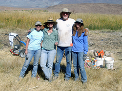 A tall man with a gray beard stands arm-in-arm with three shorter women, all dressed in jeans and T-shirts, on a dry grass plain