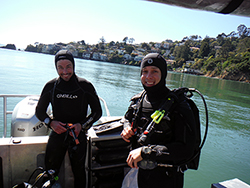 two men wearing full SCUBA gear on a boat in calm water