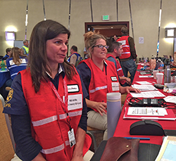 two women wearing red vests, with other people in an incident command post