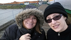 faces of two women, dressed for cold weather, on a marine dock
