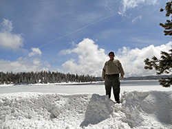 A large man stands in snow, with a lake and forested hills behind him