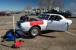 Scientist Ben Ewing's hobby is working on a white Chevy Camaro car in a parking lot