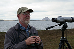 A man with a gray beard and glasses, wearing a baseball cap and dark gray jacket, stands next to a spotting scope on a tripod, near Morro Bay, with Morro Rock in the background.