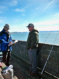 Two men on a pier, one with a clipboard and the other with a fishing pole
