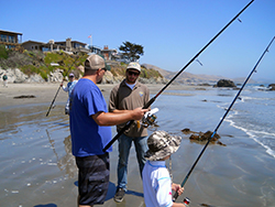 Two men and a child fishing on a sandy beach