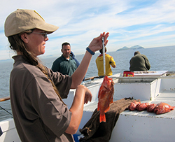 A young woman weighs a fish on a charter boat