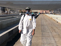 fish technician in personal protection equipment spraying down the fish hatchery with hydrogen peroxide