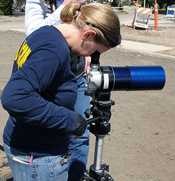 scientist looking through scope