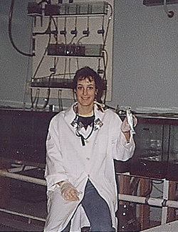 A young woman wearing a white lab coat in a laboratory with a row of metal and glass boxes behind her