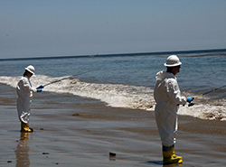 Two adults wearing hard hats and chemical-resistant jumpsuits and boots fish for samples in shallow surf during an oil spill