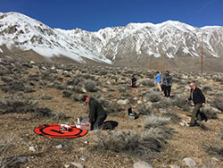 five scientist in an open field with a target to take off and land the drone with snow capped mountains and blue sky in background