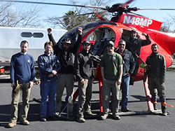 Eight-man stand in front of a red helicopter