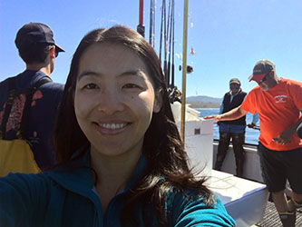 Scientist Chenchen Shen in a boat on the ocean with three other scientist and fishing poles