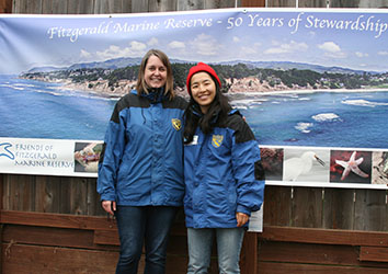 Scientist Chenchen Shen and Scientist Sara Worden standing in front of a poster