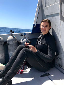 Scientist Julia Coates in a wet suit on a boat on the ocean