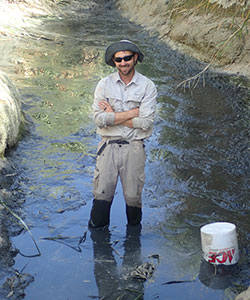 scientist, nick buckman smiling, standing in a streams with his arms crossed