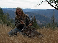 A female hunter poses in dry grass with the deer she killed