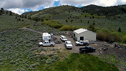 A small building, trailer, and five trucks on an isolated hill