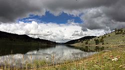Alpine lake under blue sky and mixed clouds