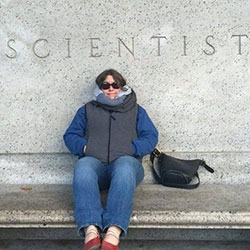 Scientist, Jennifer Garrison at the American Museum of Natural History in New York sitting on a bench under the words Scientist