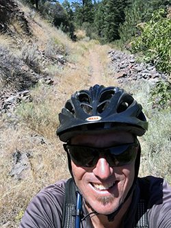 Face of a smiling Caucasian man wearing a bicycle safety helmet, with a mountain bike trail and forest behind him