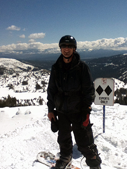 "A snowboarder dressed in black stands on a peak in a snow-covered mountain range, in front of an ""Experts Only"" sign"