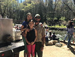 Fish Hatchery Manager, Justin Kroeze and his two daughters at the hatchery near the river with people fishing