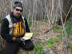 A man with a dark goatee, wearing black with an orange safety vest, kneels among dead reeds and low vegetation, holding a field notebook