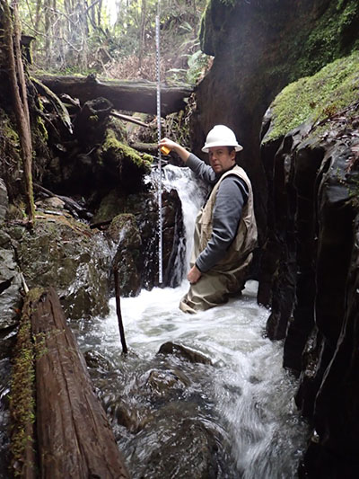 Man wearing beige waders, grey sweatshirt, beige vest and white hard hat standing in small waterfall holding long measuring stick