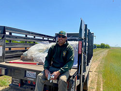 Scientist Brian Young sitting in the back of a truck with seeds
