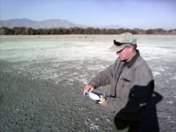A man with an electronic device in hand stands in a dry river bed with dried salt residue in background