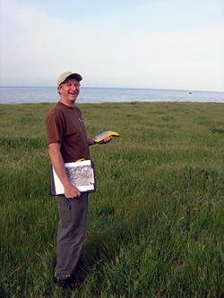 A man stands in coastal grassland with the ocean in background