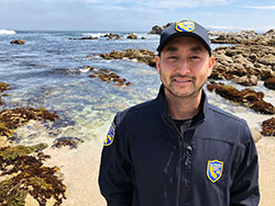 Scientist, Roy Kim, on the ocean beach in Pacific Grove