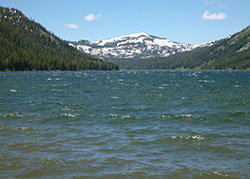 Independent Lake with white capped waves from the wind. Lake with green mountains and a snow covered mountain in background
