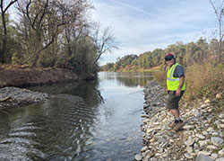 Scientist, Doug Killam standing on the rocky banks for the Sacramento River with trees and shrubs in background