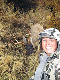 an immobiilized buck with an eye cover lies behind a pretty young woman wearing camouflage