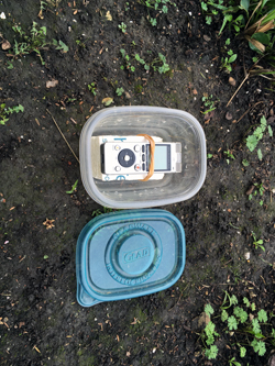 An audio recording device in a semi-clear, plastic container on dark brown ground