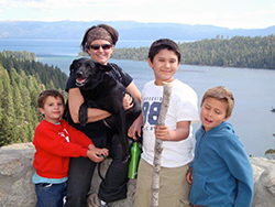 a woman holding a black labrador retriever poses with three young boys, with Emerald Bay behind them