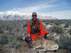 Man in orange jumpsuit kneels in sagebrush with a deer that's hobbled and blindfolded