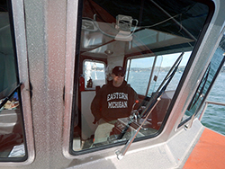 a man wearing a navy blue sweatshirt and baseball cap at the helm of a small research vessel