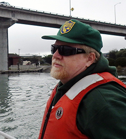 a middle-aged man wearing an orange life-vest and green baseball cap, with bay water and a concrete bridge in background