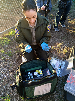 woman in fish and wildlife uniform selects small instruments from backpack
